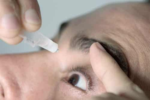 A man applying eye drops to his eyes, with his finger resting on his brow.
