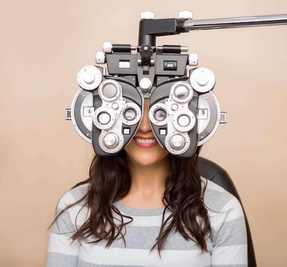 Happy young woman looking through phoropter during eye exam