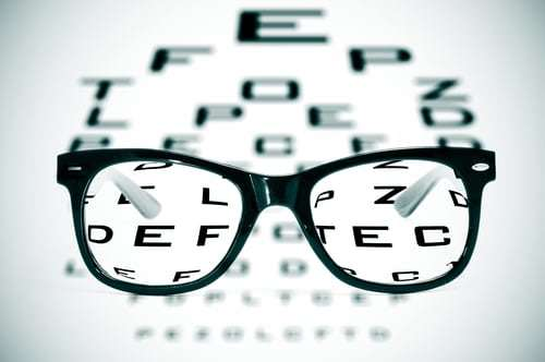 aditional eye doctor chart with a pair of black glasses in front