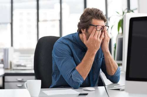 Man wearing denim shirt and glasses rubbing his eyes in front of computer.