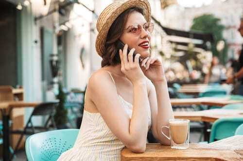 Young woman wearing transition sunglasses and straw hat, talking on the phone on cafe patio.