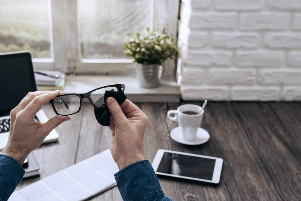 Male hands cleaning glasses over wood desk with coffee and tablet