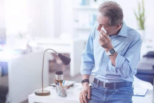 Man holding tissue to eye, in office wearing blue shirt and jeans