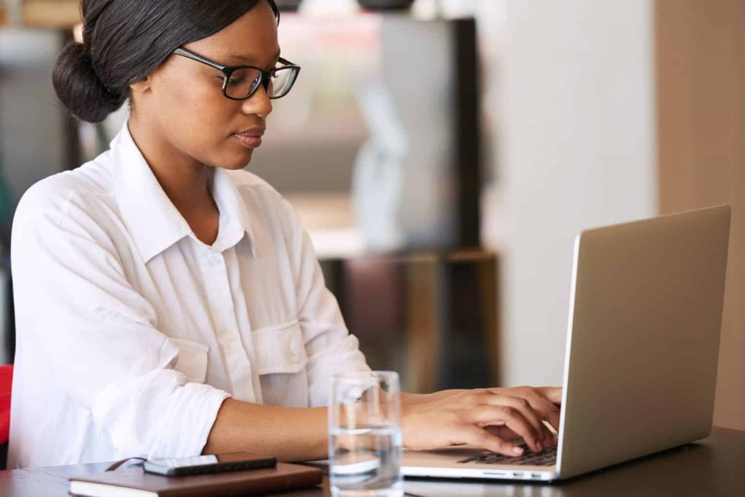 Woman wearing glasses and white shirt working on a laptop