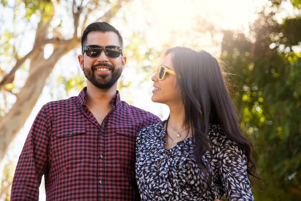 young couple wearing sunglasses, smiling outdoors