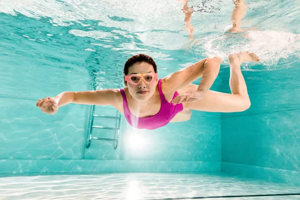 Woman swimming underwater in pool wearing goggles