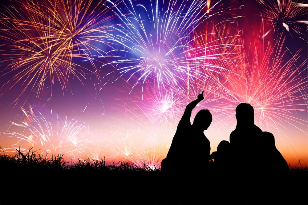 Colorful fireworks, silhouette of family watching in grass