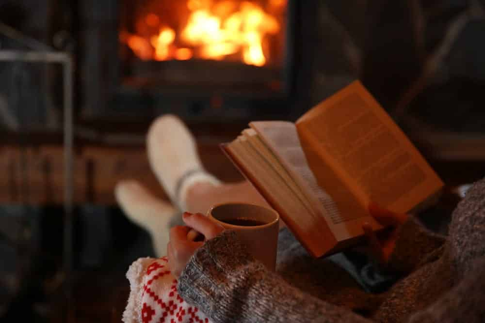 Woman Reading in the Dark by a Fire with a Hot Beverage