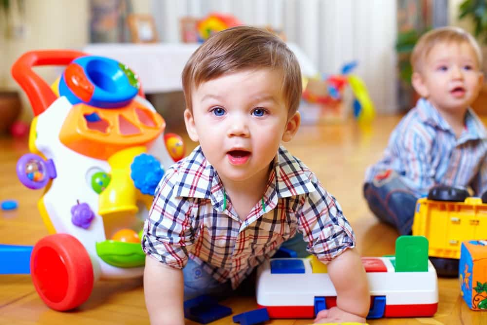 Curious toddler playing in a nursery, another child in background