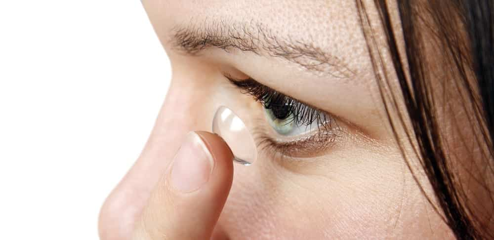 Close-up of girl placing contact in eye