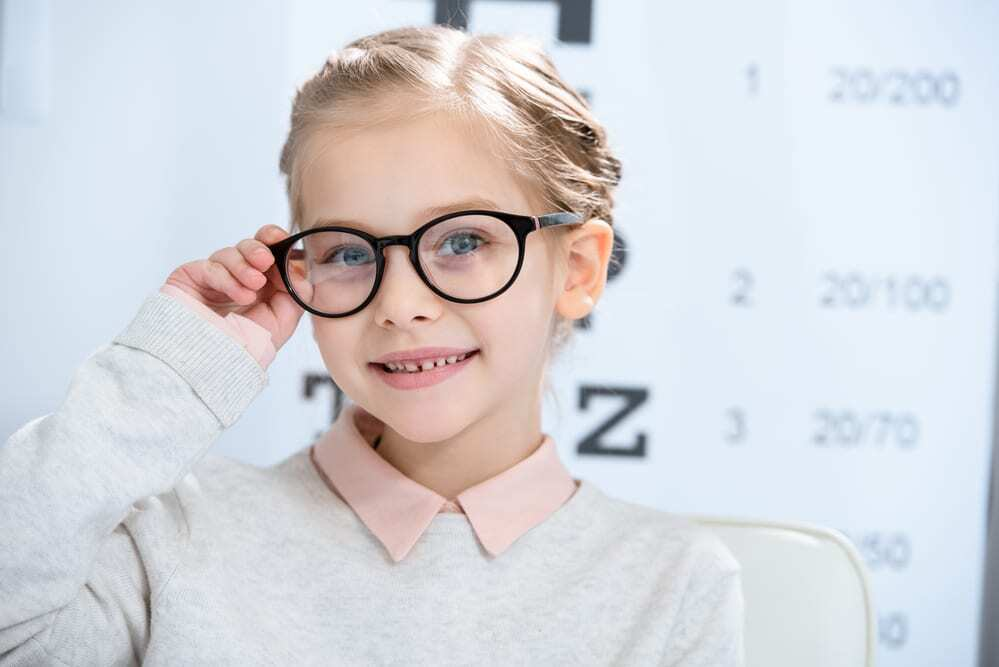 Smiling little girl wearing thick black glasses, looking at camera, eye test in background