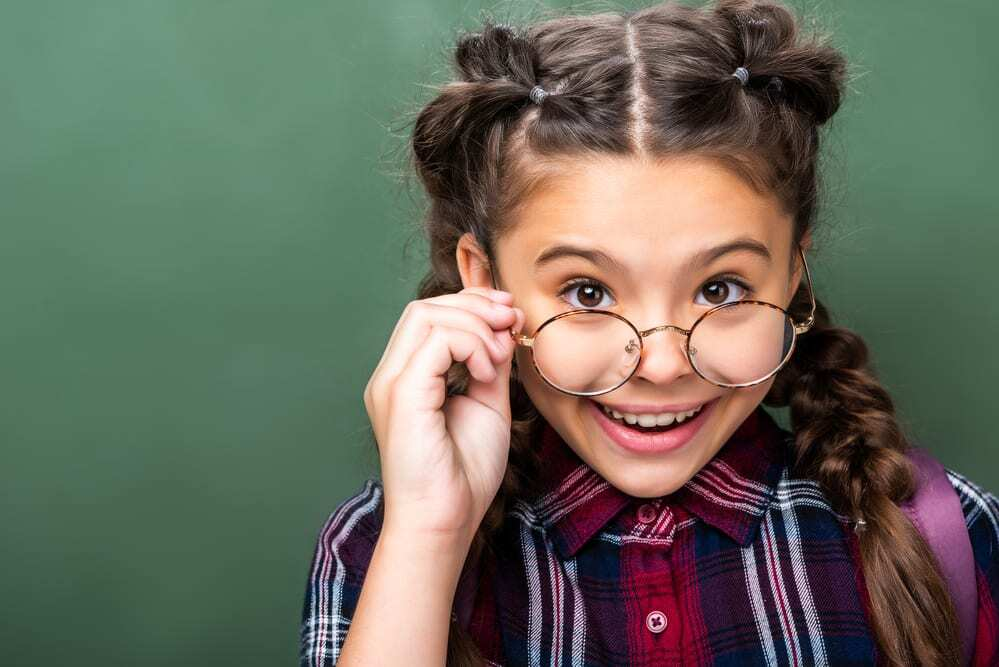Smiling young girl wearing glasses, lowering them to the tip of her nose to look over the frames