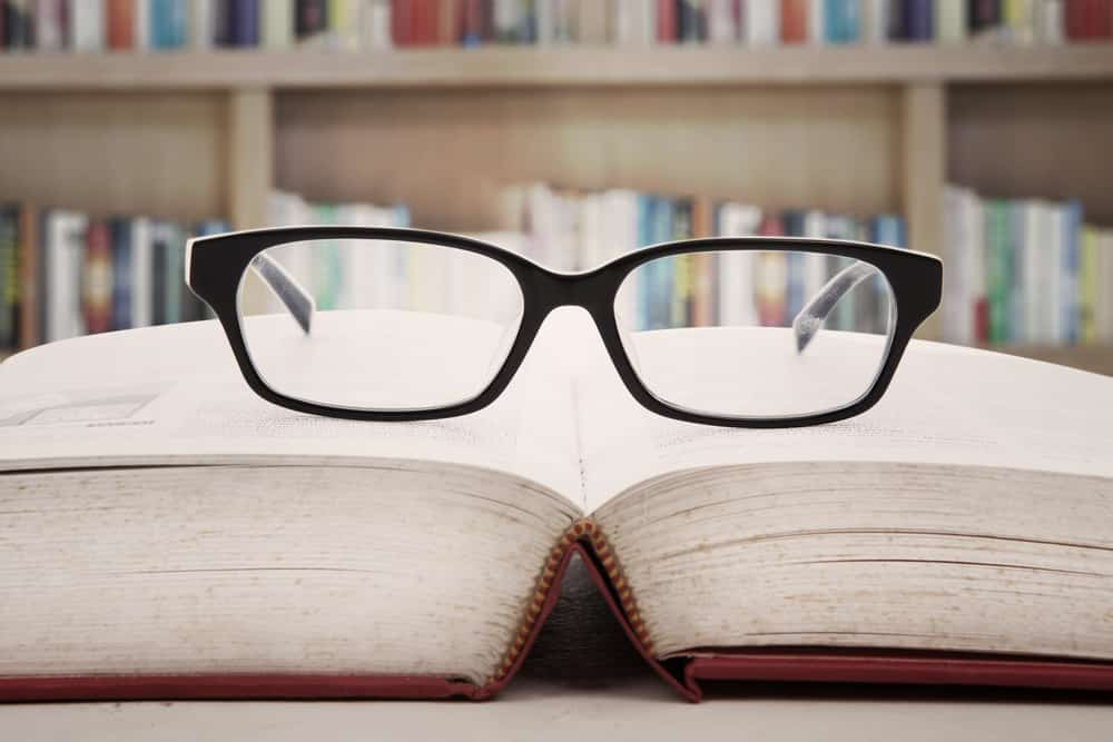Reading glasses sitting on pages of open book