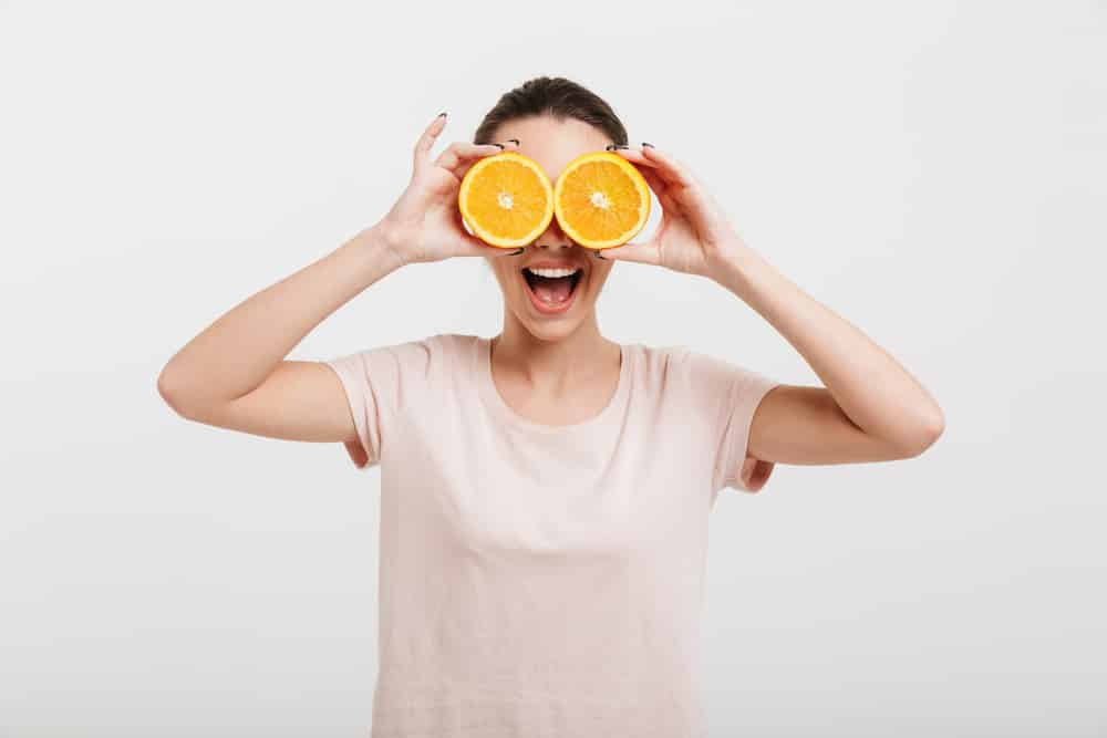 Smiling young woman holding a halved orange in front of her eyes