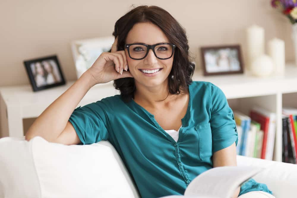Smiling woman wearing reading glasses, holding open book