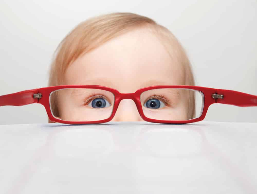 Baby looking through glasses set on table
