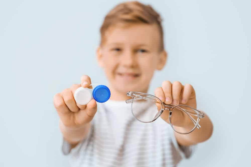 Young smiling boy holding out glasses and contact lens case