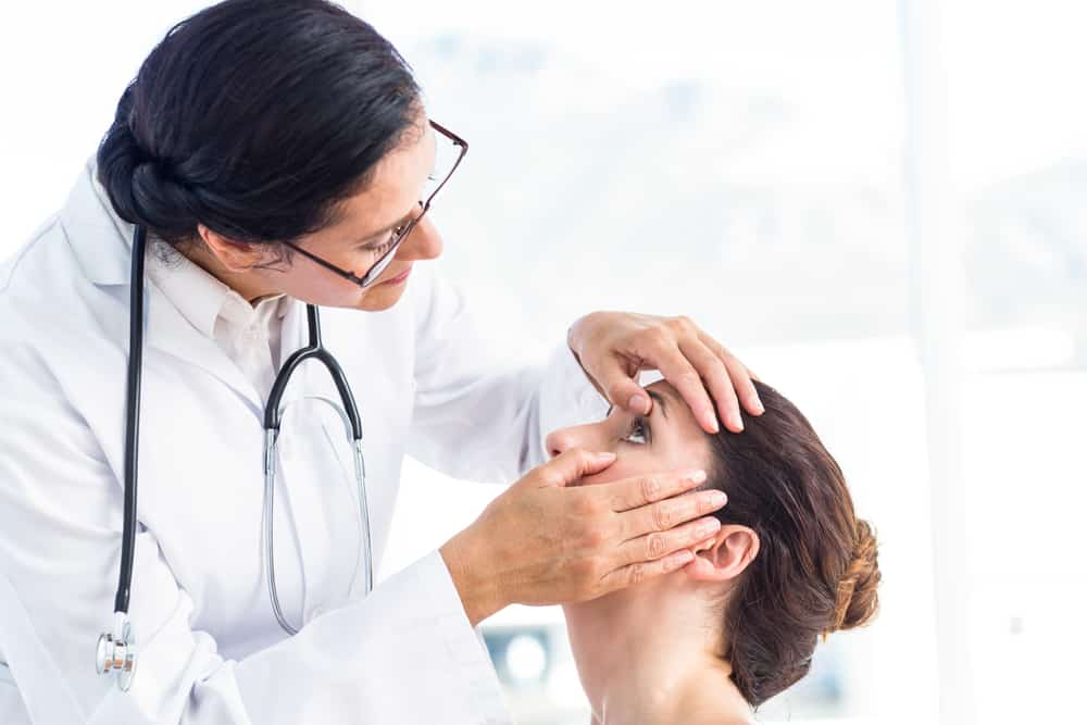 Doctor examining young female patient's eyes