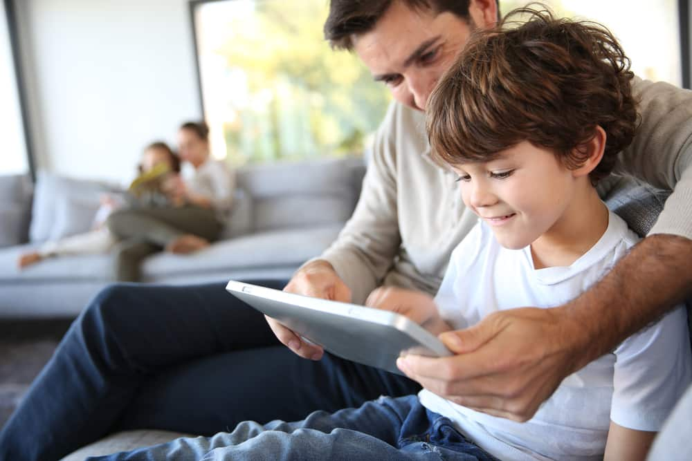 Smiling father and son using tablet in home