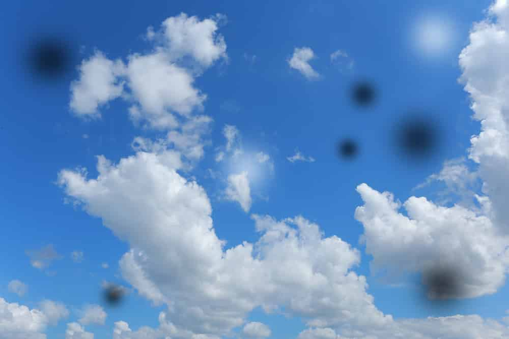Depiction of eye floaters on photograph of blue sky with clouds